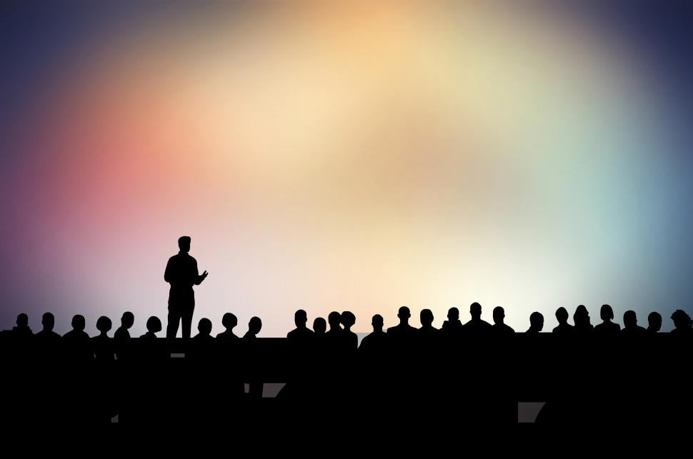 Silhouette of a person standing and talking to a group.