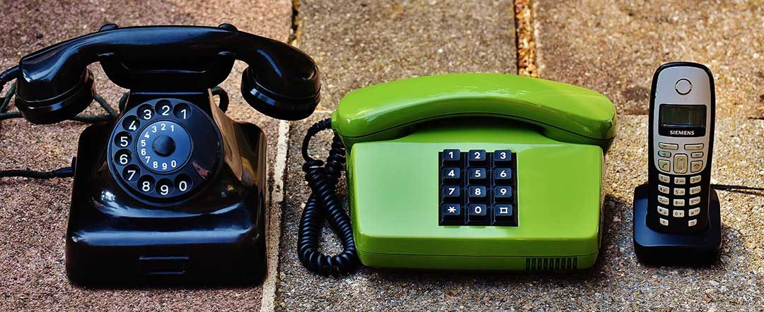 Three different styles of older telephones: rotary, push button and cordless.