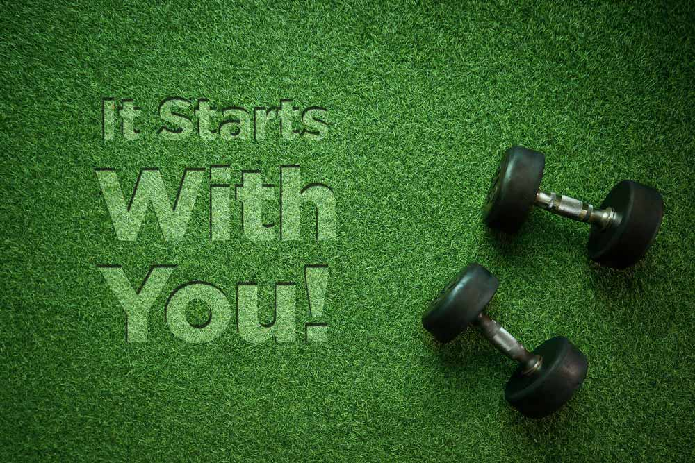 Dumbells sitting on grass with the book title, It Starts With You!, on the left side