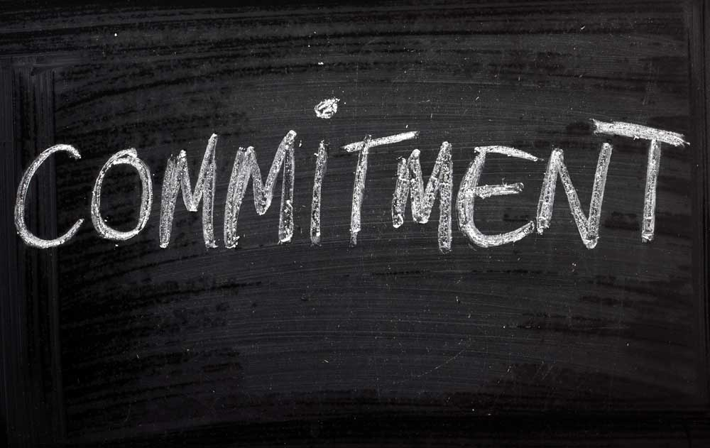 The word, Commitment, written on a chalkboard