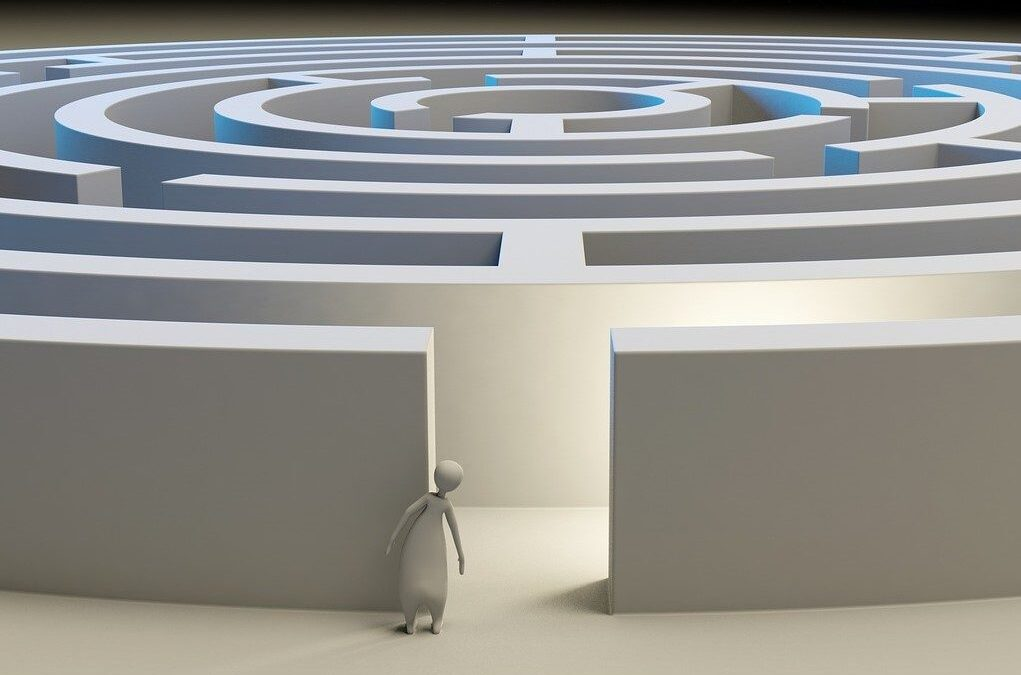 Figure looking at the entrance of a maze.