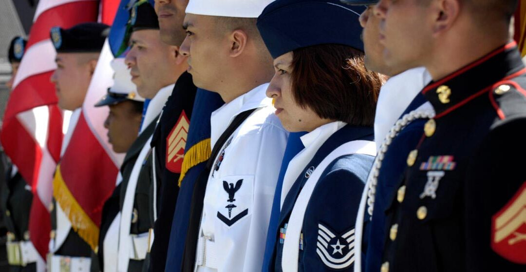 A line of people wearing uniforms of the different branches of the US military.
